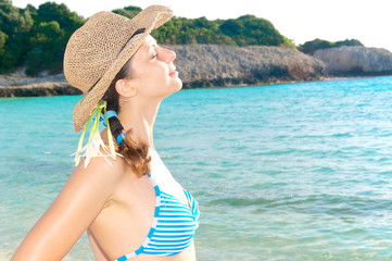 Beautiful girl with straw hat gets the sun in a blue bay