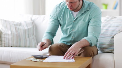 man with calculator, papers and money at home