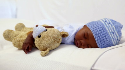 Baby boy sleeping in crib with teddy bear