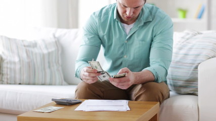 man counting money and making notes at home