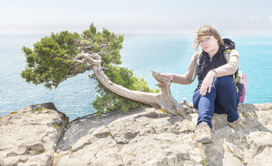 woman tourist sits on a cliff above the sea