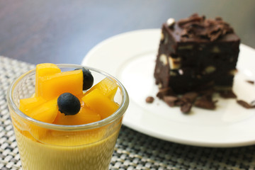 mango pudding in a glass and chocolate brownie as background, ca
