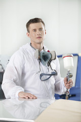 young man standing and holding airbrush.