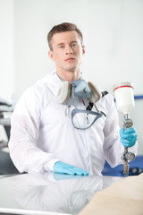 young man standing inside and holding airbrush.