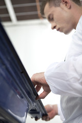young man repairing car door.