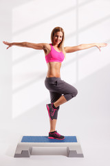 Beautiful young woman doing exercises on aerobic step