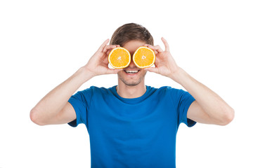 young man holding two oranges.