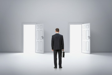 Backview portrait of businessman in front of two doors