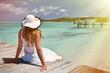 Girl on the wooden jetty looking to the ocean. Exuma, Bahamas
