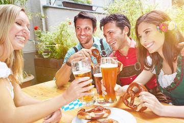 Freunde in Biergarten in Bayern stoßen an