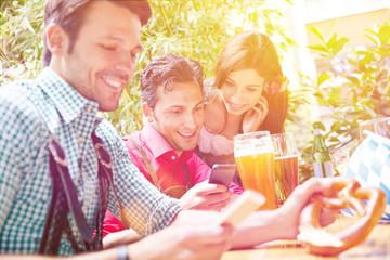 Freunde im Biergarten schauen auf Smartphone