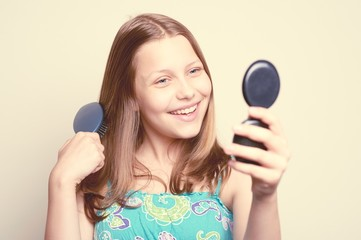 Teen girl holding hairbrush and looking at the mirror