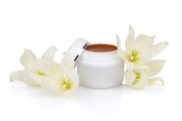 Open jar with the cosmetic cream and flowers