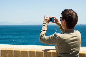 Woman taking photo of a blue sea