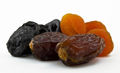 dried dates, prunes and apricots on white background