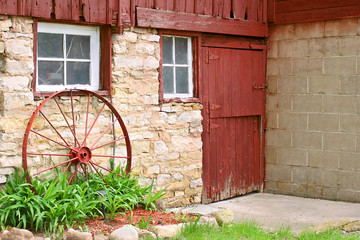 Antique Wagon Wheel Leaning on Old Stone Barn Wall