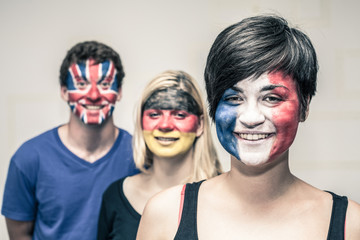 Happy people with painted flags on faces