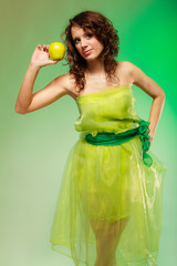Spring or summer food. Woman girl in green dress holding apples