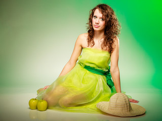 Spring or summer. Young woman girl in green dress sitting