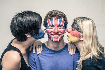 Happy friends with painted flags on faces kissing