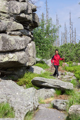 Frau wandert an Felsformation entlang