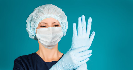 Doctor or nurse wearing surgical mask, cap and putting gloves.