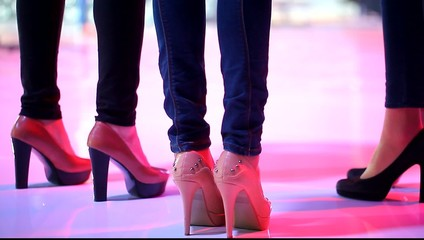 shapely female legs in jeans and fashionable shoes on high heels