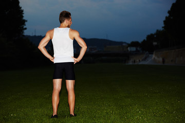Athletic muscular runner at evening jog in the park