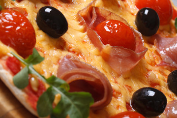 pizza with prosciutto ham, tomatoes, black olives macro texture