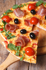 Sliced ​​pizza with ham, tomatoes, olives and arugula vertical