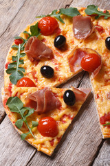 Pieces of pizza with prosciutto, arugula and tomatoes on wooden