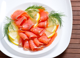 Sliced salted salmon served with lemon