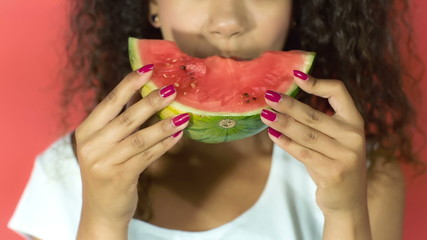 Pretty black girl eating watermelon on red background