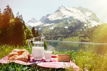 Milk, cheese and bread served at a picnic on Alpine meadow, Swit