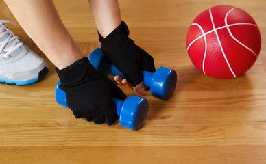 Woman working out with small weights on wooden gym floor