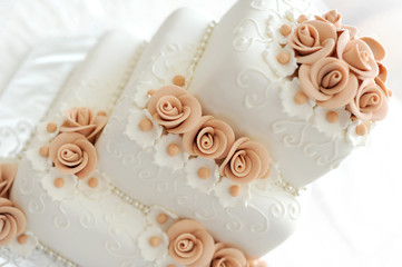 Wedding cake with pink flowers on light background