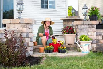 Happy elderly Grandma potting up plants