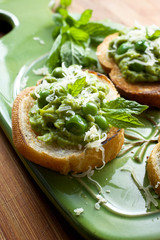 Canape with green peas pesto, cheese and fresh mint