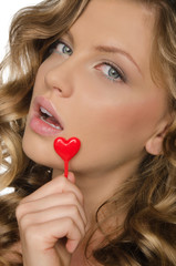 Woman holding heart in open mouth