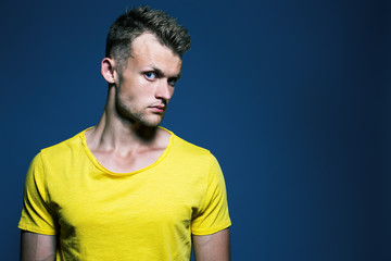 Emotive portrait of muscular young handsome man in bright yellow
