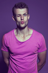 Emotive portrait of muscular young handsome man gives a kiss in