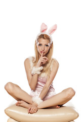 lovely blonde girl in rabbit costume with finger on her mouth