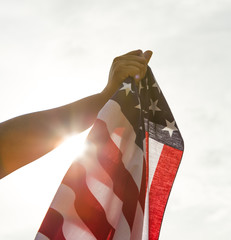 Hand hold American flag with sun light