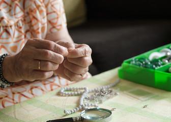 Hands of senior woman making a necklace
