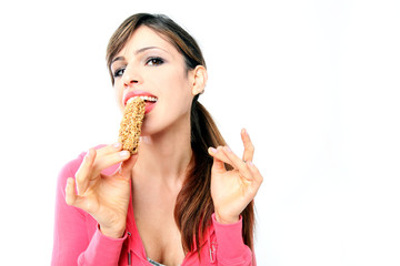 Beautiful girl eats cereal bar