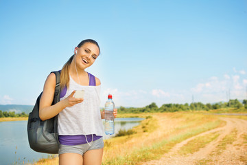 Young runner woman with smart phone outdoors in summer
