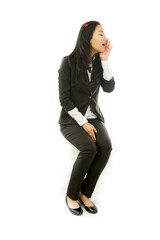 Asian young businesswoman sitting on stool in devil horns