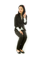 Asian young businesswoman sitting on stool in devil horns with