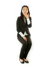Surprised attractive Asian young businesswoman sitting on stool