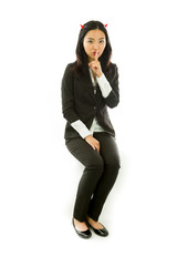 Asian young businesswoman sitting on stool in devil horns finger
